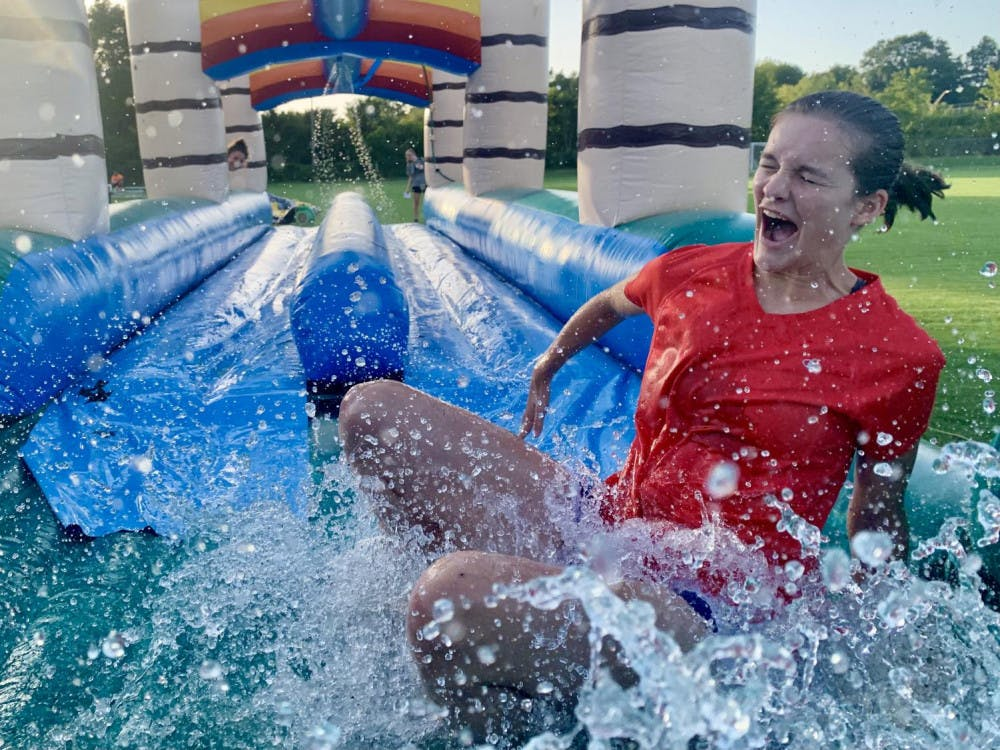 Mercer student Mary Lichtenwalneer makes her way to the end of a slip-n-slide at Rec the Night at the new Outdoor Recreation Complex.