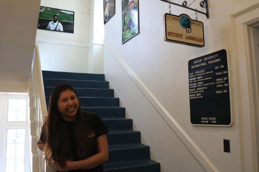 """Lisa Fortin, a study abroad ambassador for Mercer's study abroad office, poses for a picture under the """"Study Abroad"""" sign in Ryals Hall in February."""