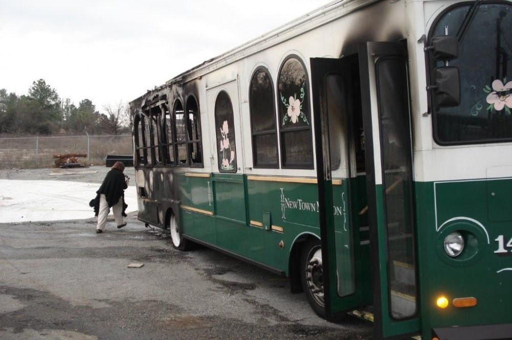 A reporter snaps shots of the remains of the Miss Molly trolley Friday morning after it spontaneously combusted just hours before. Miss Molly caught on fire moments after making its last run of the night Thursday.