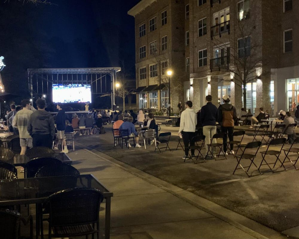 Members of the Mercer community watch the March 8 men's basketball game at the watch party in Mercer Village.