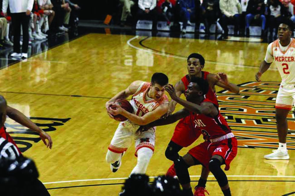 Bears junior guard Djordje Dimitriovic (No. 0) protects the ball as he drives past several VMI defenders.