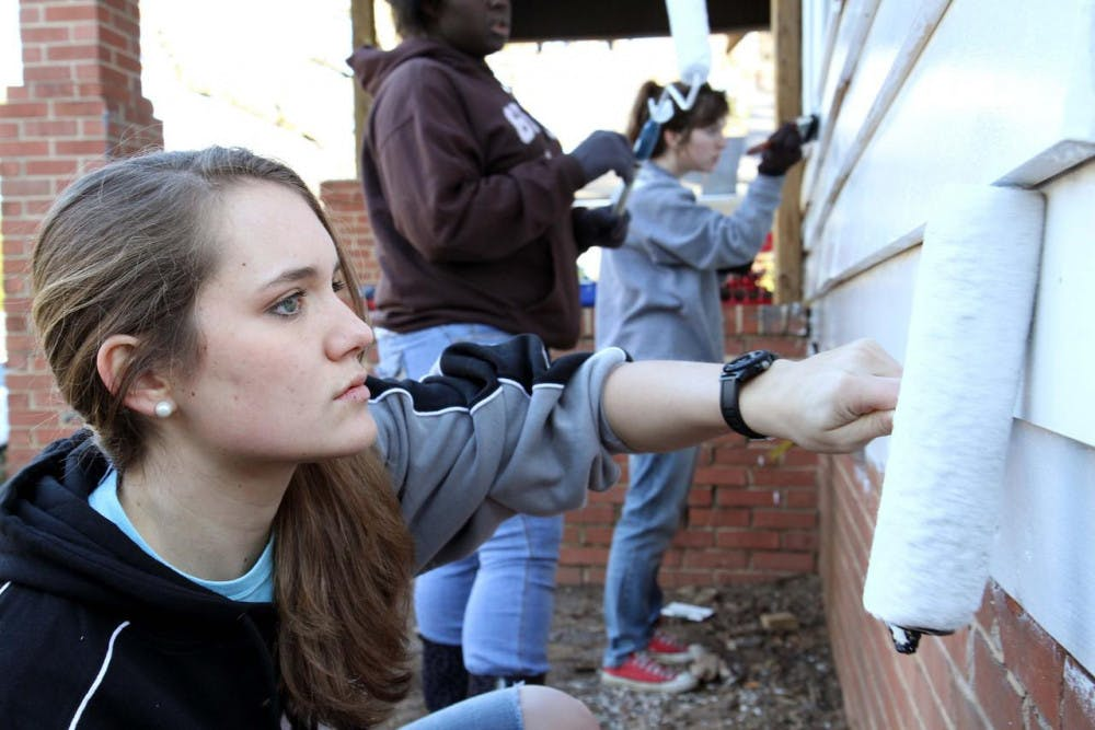 Janea Feeney helps paint the exterior of a house as part of the 2014 MLK Day of Service.