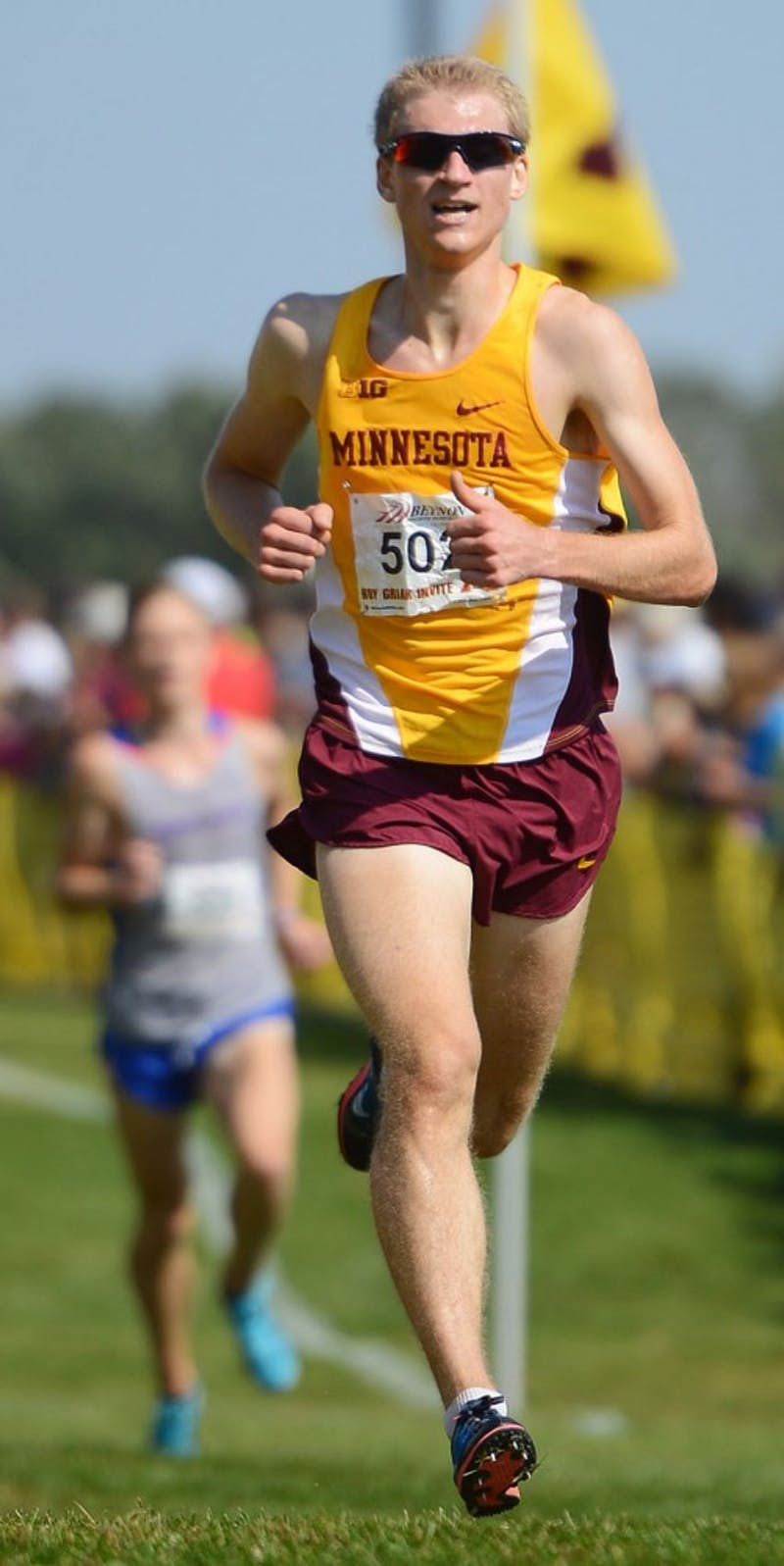 Junior Aaron Bartnik runs the final stretch of the Division 1 Men's race at the Roy Griak Cross Country Invitational at the Les Bolstad Golf Course on Saturday, Sept. 27, 2014.