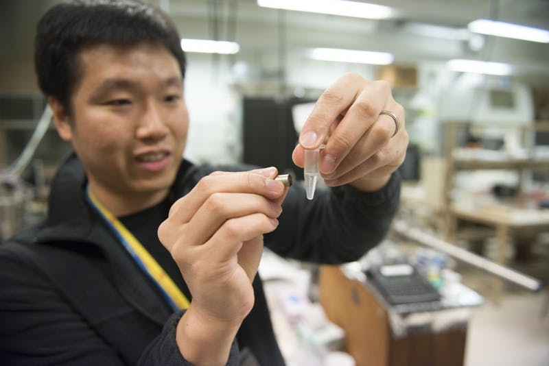 Ph.D candidate Joseph Um holds a magnet up to a vial of nano wires in a clear solution on Tuesday, Feb. 12 in Keller Hall on the East Bank campus.