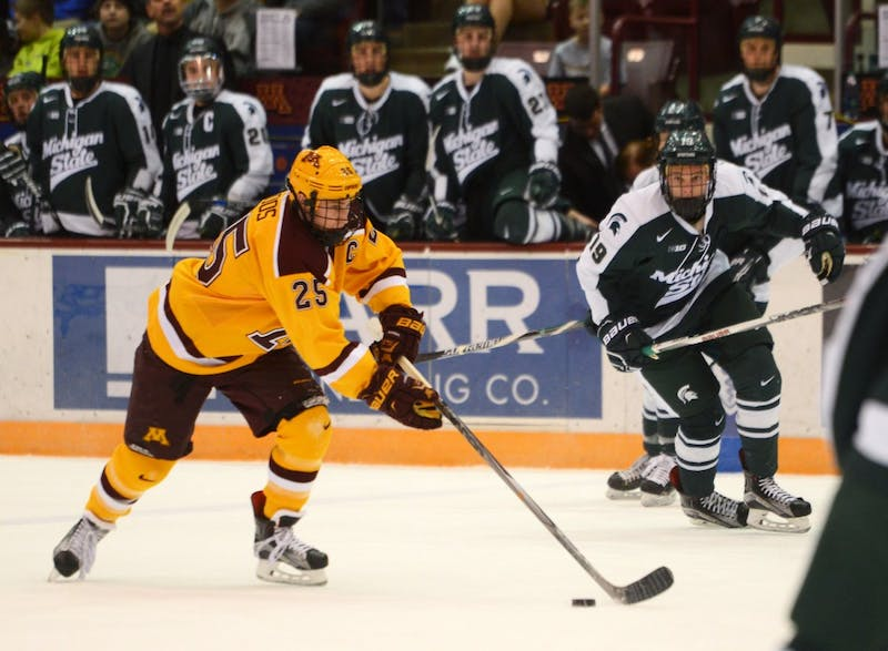 Gophers forward Justin Kloos drives the puck against Spartan defenders at Mariucci Arena on Saturday. Minnesota swept Michigan State to close the series with a final score of 3-1.