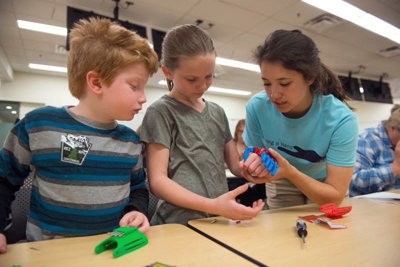 Six-year-old John Donohoo, left, and Kelly Hannon assemble a 3D printed prosthetic hand with cousin Elizabeth Moy, a member of Engineering World Health. The student group hosted Giving a Hand, an event at which attendees built prosthetic hands for children in Honduras and Tanzania, in Moos Tower on Saturday.