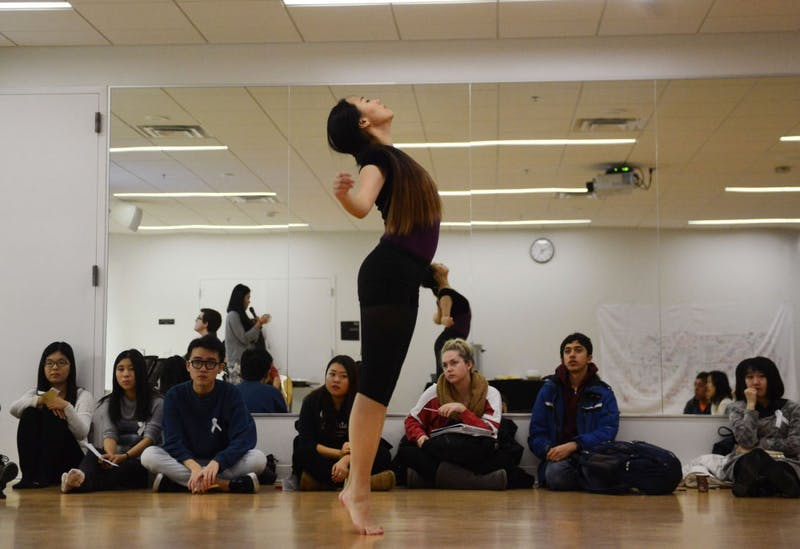 """Junior and Women of Asia event coordinator Ziyi Zhao dances to the stories shared by students at the Recreation Center Friday evening. Women of Asia hosted its first event informing students how to """"say no"""" to relationship violence."""