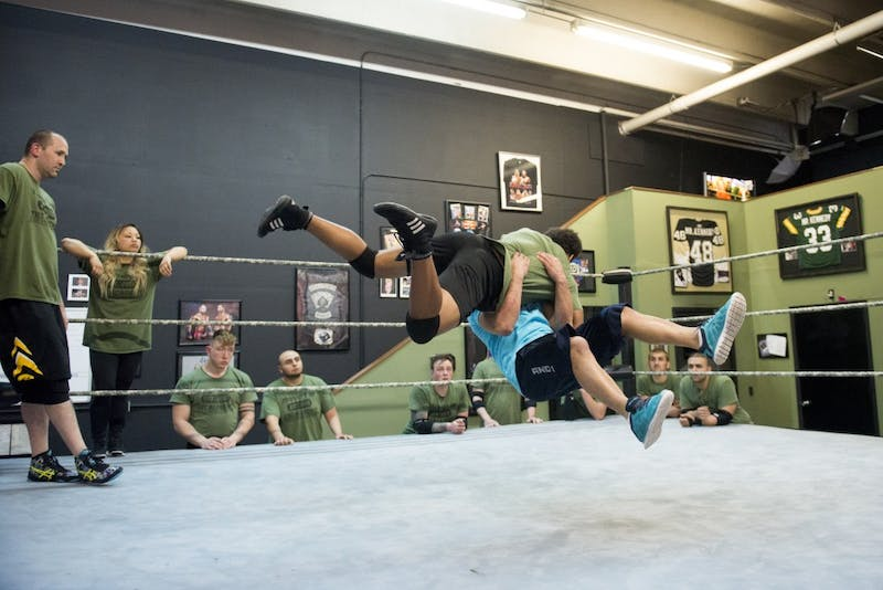 Coach Shawn Daivari demonstrates a move on a student in the ring while other students observe at The Academy in Minneapolis.