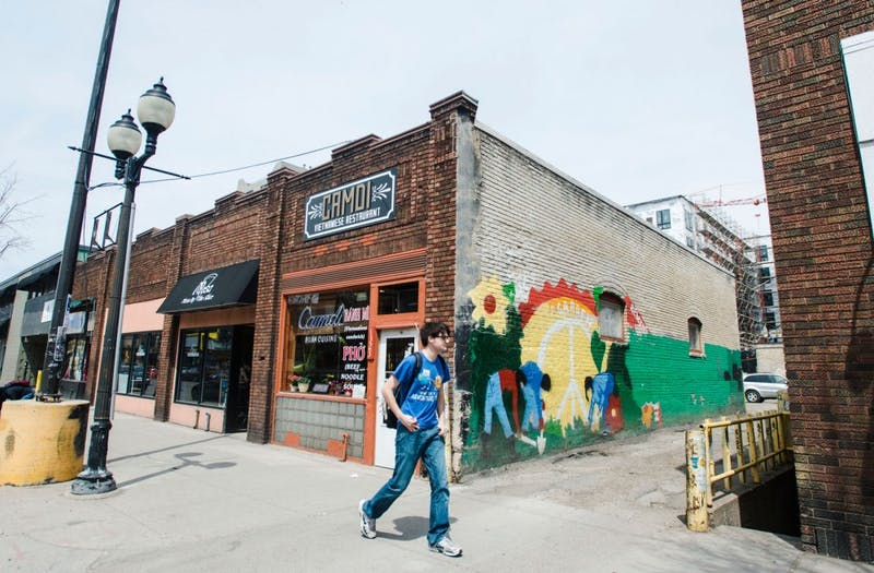 A man walks past Camdi in Dinkytown on Tuesday. The restaurant is located in one of several properties included in the historic designation study, along with Mesa Pizza and Dinkytown Tattoo.