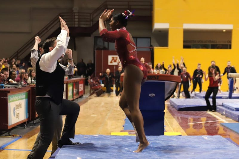 Paige Williams is congratulated by her coach after vaulting on Saturday, March 2 at Maturi Pavilion.