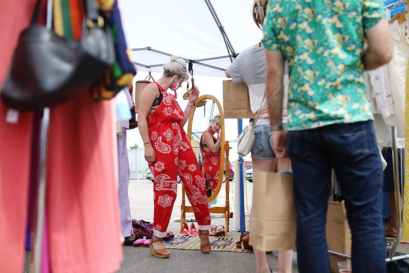Alexandria Cochran tries on a red overall outfit at the launch of the Minneapolis Vintage Market on Sunday, June 24.