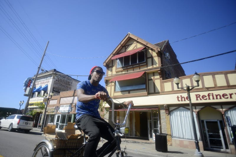 University of Minnesota alum and Sssdude-Nutz co-owner Bradley Taylor rides his bike to Open Streets Dinkytown to pass out free doughnuts on Saturday, Oct. 1, 2016 in Dinkytown. Sssdude-Nutz has just celebrated its one year anniversary and Tim Horton's has signed a lease to move in next door.
