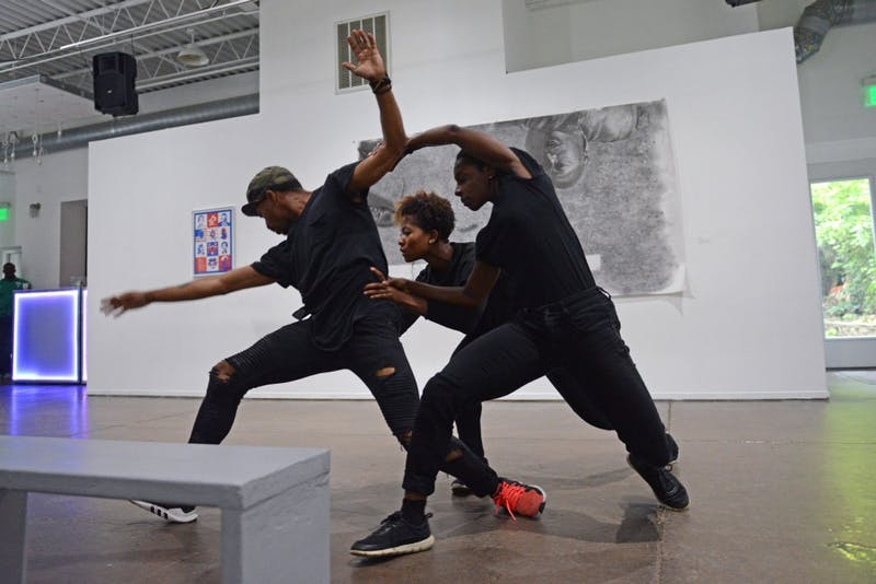 """Alanna Morris-Van Tassel, Darwin Black and Taylor Collier perform at """"The Shop,"""" an art exhibition focused on black barbershop culture, on July 1."""