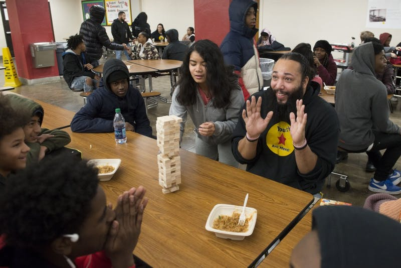 """Community Outreach team member Mark Woods plays a game of Jenga with students at Patrick Henry High School  on Friday, Dec. 7. Woods sees him self as a """"positive instigator"""" who is able to offer mentorship to youth outside of typical school and athletic environments."""