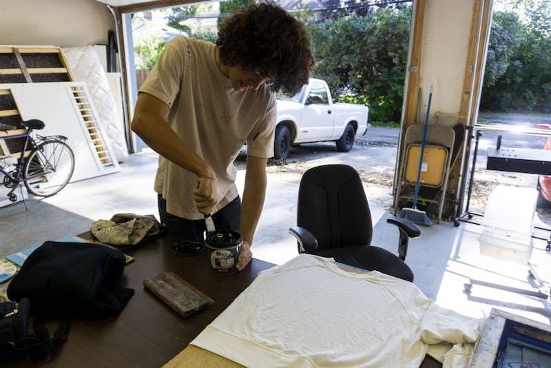 "Drew Kinkade works on screen printing t-shirts for his clothing brand, ""Flavor World,"" in his garage in the Como neighborhood on Monday, Oct. 7."