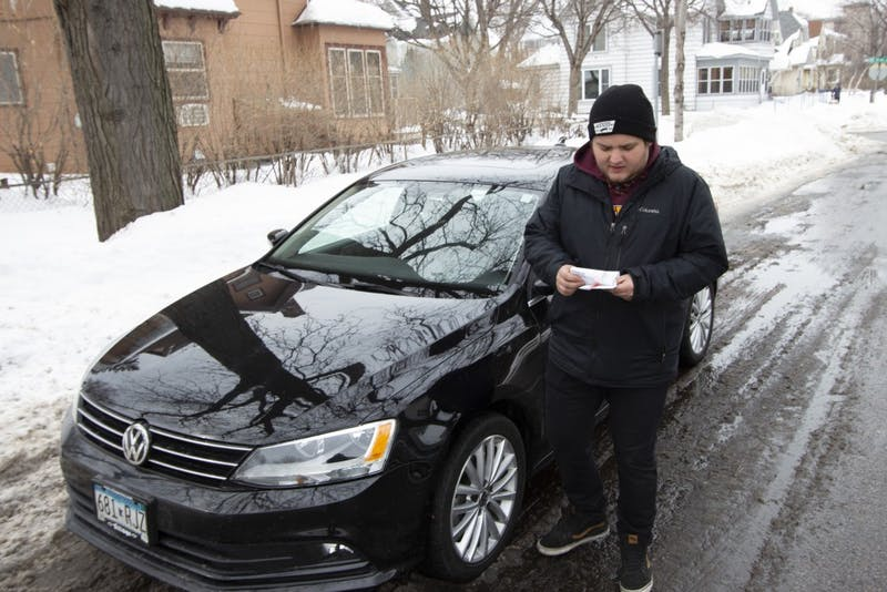 "Cameron Eller removes a parking ticket he got after being confused about where he should park because of Minneapolis' winter parking restrictions on Saturday, March 9, 2019. Eller received the ticket a day before, but had been leaving it on his car for ""keepsake."""