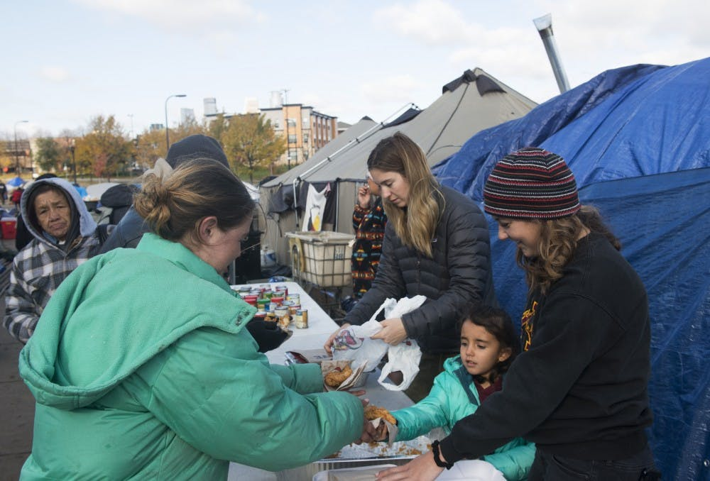 On the other side of Hiawatha Avenue, life in a tent city goes on