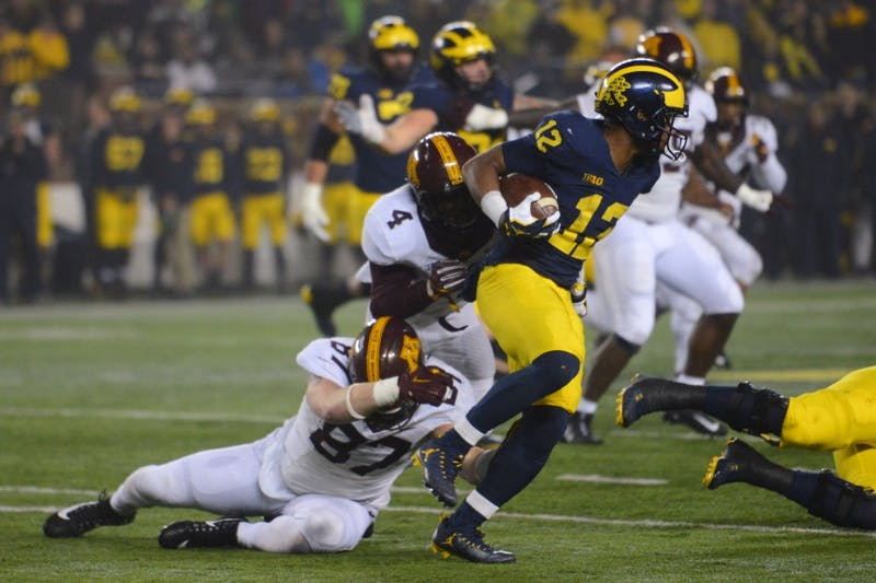 Defensive lineman Nate Umlor and defensive back Adekunle Ayunde attempt to tackle Michigan quarterback Chris Evans on Saturday, Nov. 4, in Ann Arbor, Michigan. The Gophers lost to the Wolverines 33-10.