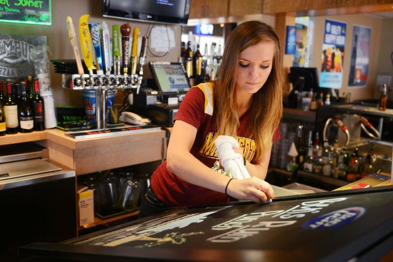 Psychology and criminology junior Kayla Latarte writes specials on a board Friday at Campus Pizza, where she is a bartender.