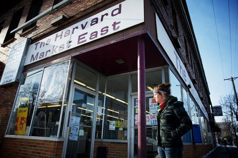 Assistant Manager Dana Kabitzki takes a cigarette break Saturday outside the Harvard Market in Stadium Village.  The corner store will close after 106 years of operation on campus.