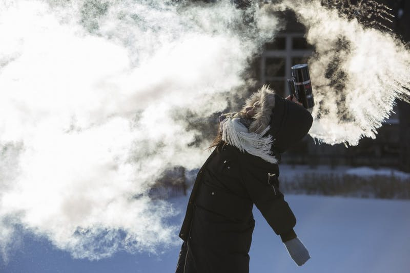 Electrical Engineering sophomore Yilia Yang throws hot water into the air to watch it freeze on Wednesday, Jan. 31 in the East Bank Mall. Yang had the day off because classes were cancelled due to extremely low temperatures.