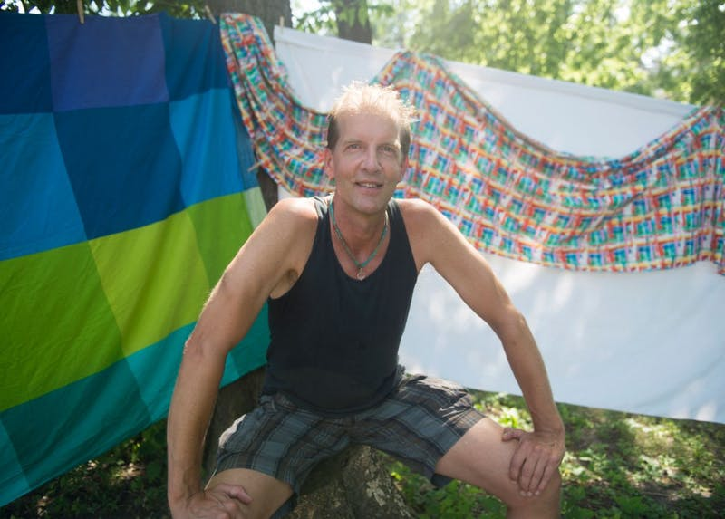 """Actor Damiian Lang poses in the backyard of his house, the future venue for his one-man show """"Glorious Garbage, Good Grief!"""" Lang's show is a part of the greater Fringe Festival, which hosts live theater throughout Minneapolis July 30 through August 9."""