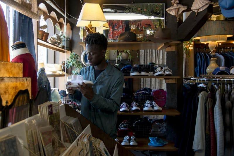 Justin Ofori-Atta looks at shoes inside Corner Store Vintage on Thursday, Aug. 29.