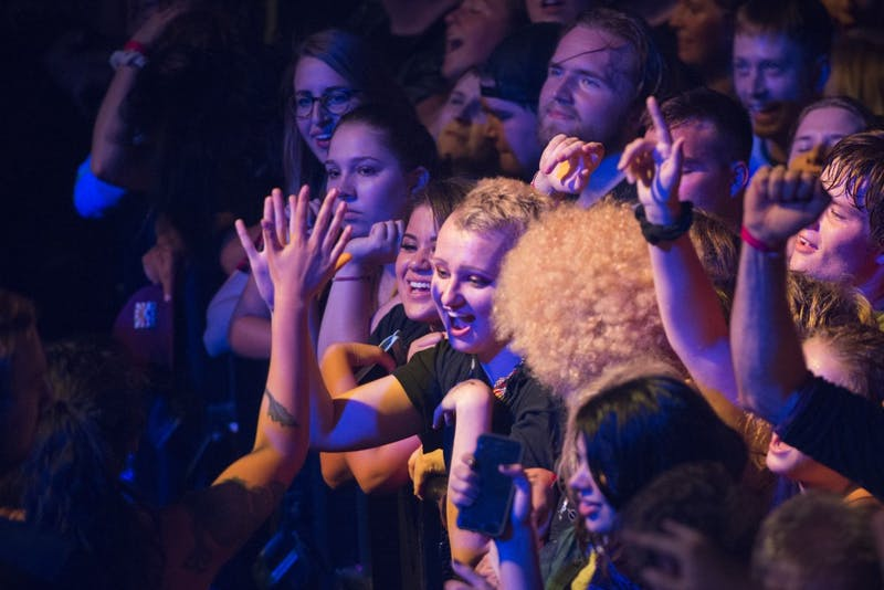 A member of the crowd high-fives a person who was escorted out of the photo pit for crowd surfing on Friday, Sept. 7 at the First Avenue Mainroom.