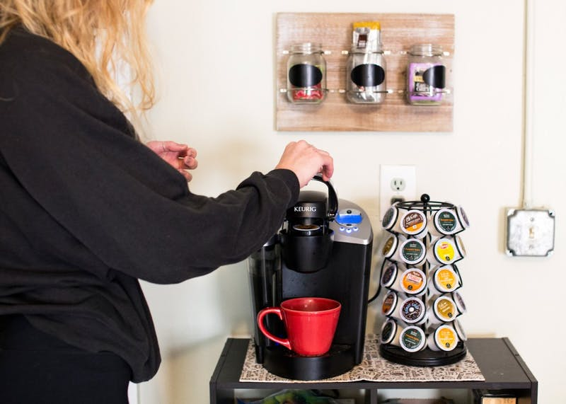 Sophomore Cece Sjoquist places a K-Cup in the Keurig she shares with her roommates in her Dinkytown apartment on Monday.