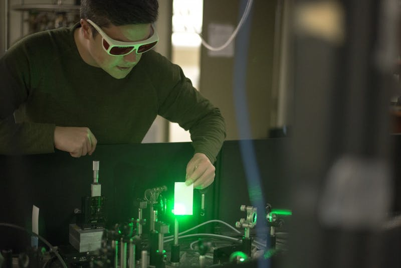 Harrison Frisk, a fifth-year graduate student in the Department of Chemistry, shows the power of the lasers in his ultrafast laser spectroscopy table. The lasers come from a single unit and are bounced off crystals, some of which are grown in the lab, before they reach a special chamber that holds a two-dimensional crystal which allows Frisk to study the physics of the electrons in the light.