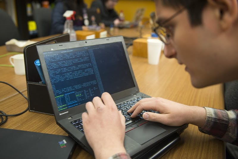 """Electrical engineering sophomore Sina Roughani operates a terminal that he uses to capture recorded data from the University's """"people search"""" in Keller Hall on Thursday, Feb. 28."""