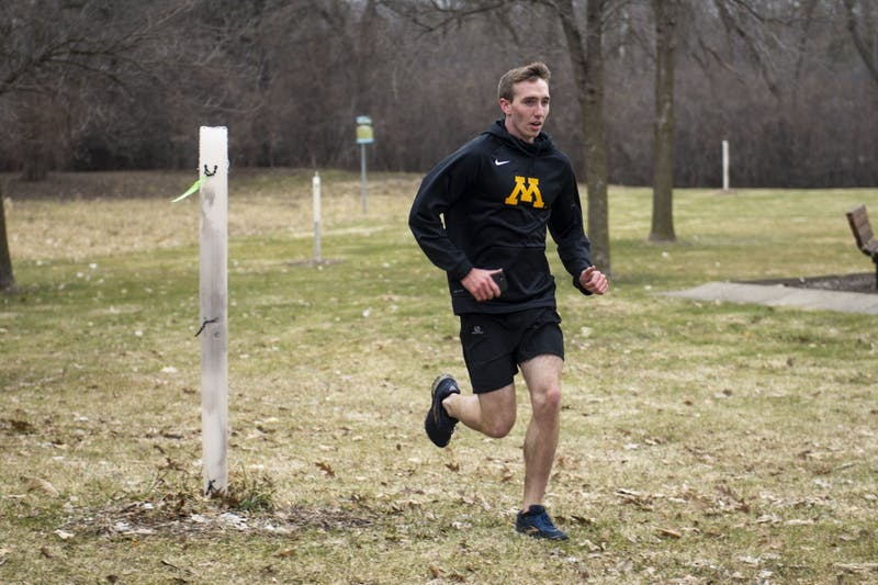 "Sophomore Austin Morrow completes the last lap of his run at Hidden Ponds Park in Eden Prairie on Saturday, March 28. ""Running is a big part of physical fitness,"" he said."