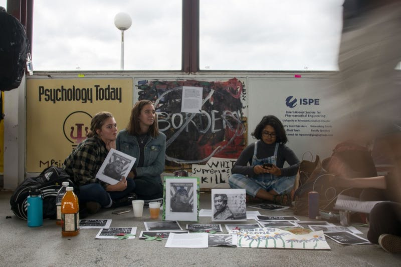 "Student protestors sit in front of the College Republicans' ""Paint the Bridge"" panel on Washington Avenue Bridge on Friday, Sept. 27, 2019. This is the fourth consecutive year that the student group's mural has been vandalized."