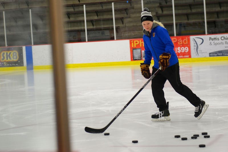 Three-time Olympian and University graduate Noora Räty gathers pucks during a private lesson for a young goalie early Tuesday morning at the Eagan Civic Arena.