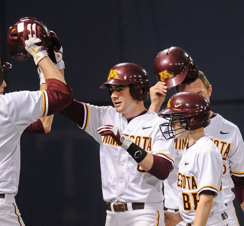 Minnesota catcher Matt Halloran celebrates with his team after hitting a two-run home run against Iowa on Friday, April 27, 2012, at the Metrodome.