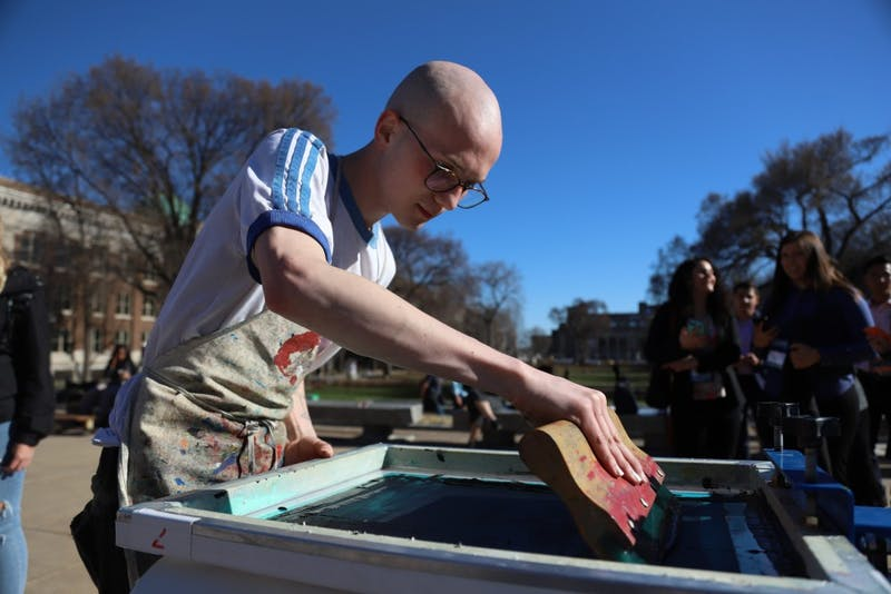 Barthollomew Presby makes environmental-friendly shirts at the Environmental Justice Earth Day celebration in Northrop Mall on Friday, April 19.