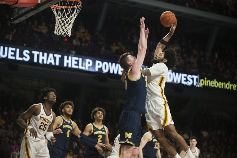 Senior Jordan Murphy jumps to dunk the ball on Thursday, Feb. 21 at Williams Arena in Minneapolis. The Gophers lost to Michigan 69-60.