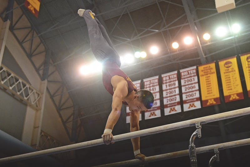 Freshman Justin Karstadt competes on the parallel bars at the Sports Pavilion on Feb. 13, 2016.