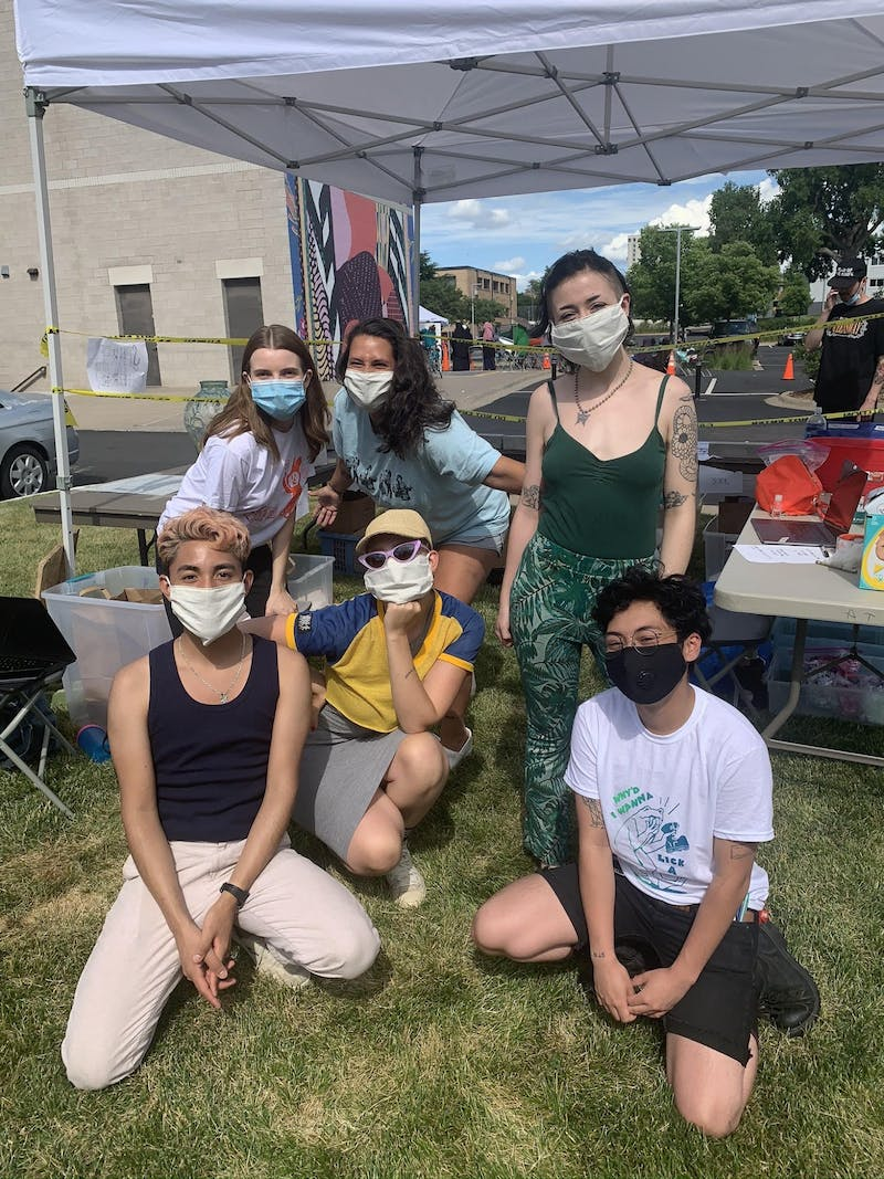 Ursula Arhart, Kristina Johnson, Cecily Bohman, Jaime Candia, Rebekah Nygard, and Nico Sardina,  from back left to front right, pose for a picture while working at the People's Library T-Shirt pop-up shop. (Photo courtesy of The People's Library)
