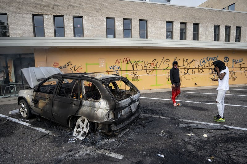 A burned out car is seen the morning after a second night of protests that turned violent near the Minneapolis Police 3rd Precinct following the death of George Floyd. Dozens of businesses were vandalized and firefighters were still working to control several blazes still at hand on Thursday, May 28.