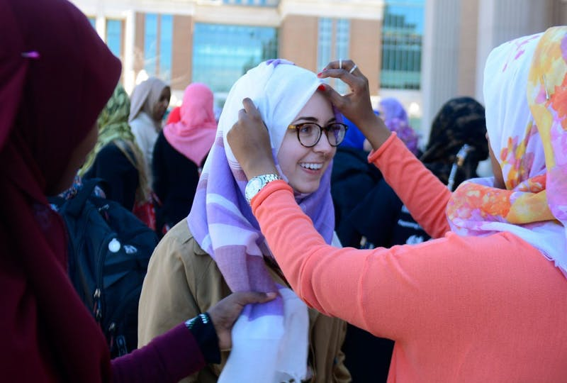"""Junior Anastasia Press (center) smiles as Freshman Megan Abdirahman (right) helps her put on a hijab for """"Hijab for a Day"""", an event put on by the U of M Al-Madinah Cultural Center for Islam Awareness Week. The event was designed to demonstrate the importance of wearing the Hijab for Muslim women."""