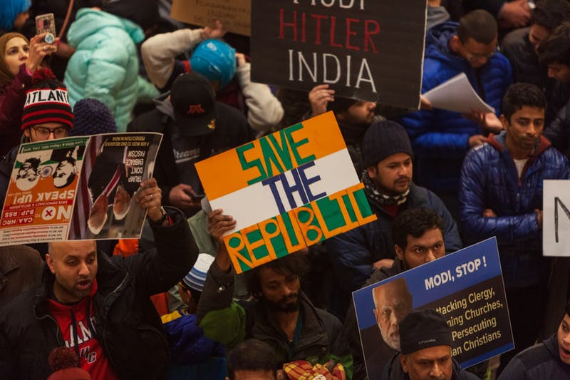 Attendees hoist protest signs at an event opposing India's recent passage of the Citizenship Amendment Act at the Minnesota State Capitol Building on Sunday, Jan. 26. This legislation offers Indian citizenship to refugees of several religious groups, but does not apply to Muslims, despite their making up nearly 15% of the Indian population.