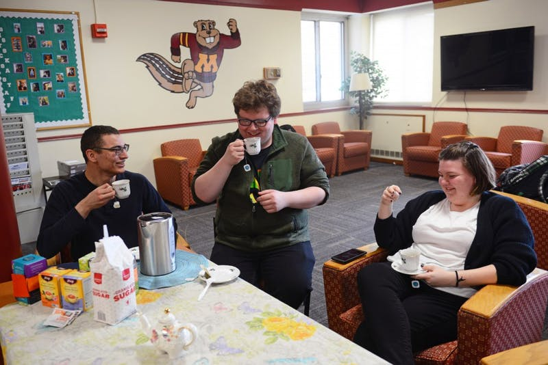Zachariah Little, center, engages with Daymian Snowden, left, and Lauren Foley at his tea club in Comstock Hall on Wednesday, April 11. He runs this club every Wednesday and Friday at 4 p.m.
