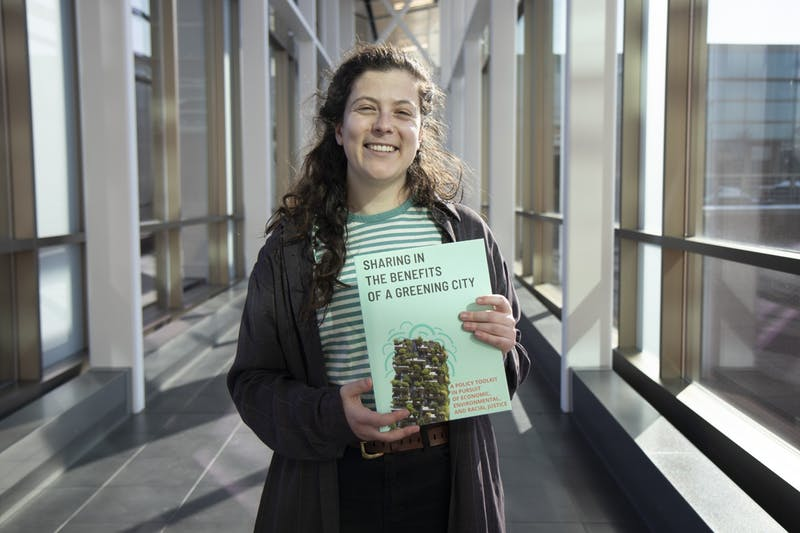 "Mira Klein, CREATE Initiative research associate, poses for a portrait on the University of Minnesota campus on Friday, Feb. 21. Klein holds ""Sharing in the Benefits of a Greening City,"" a toolkit meant to address the interactions of gentrification and justice in Green New Deal planning, including city parks."