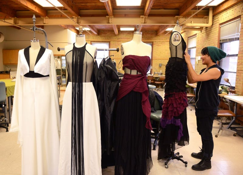 """Apparel design major Lee Tran makes final alterations to his four-piece collection for the upcoming senior fashion show, """"Identity"""", in McNeal Hall on Sunday."""