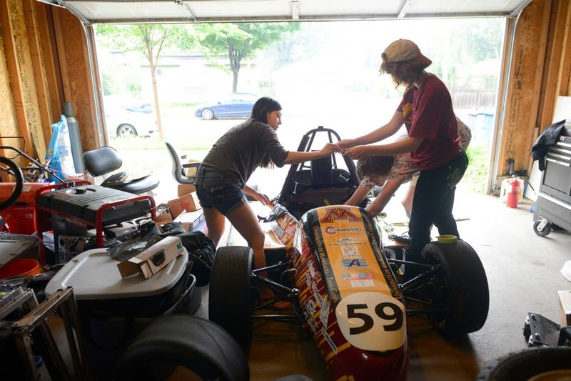 Justine Chu, Abby Hempy, and Alex Melin work on the Formula SAE car built by CSE group Gopher Motorsports in Minneapolis on Monday. The group members, who compete in the global Formula SAE series against other universities each year, often work on the car inside of a team member's garage and are unhappy with the resources they have gotten from the University while building their vehicle.