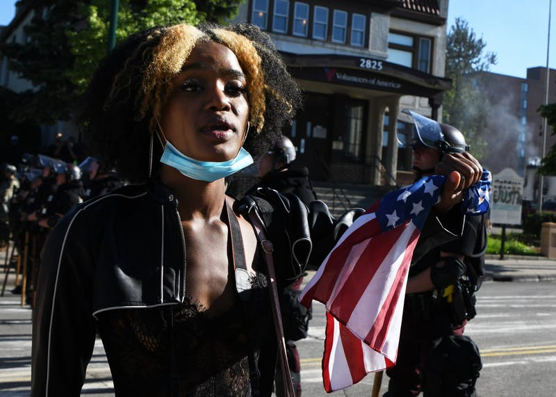 "Akilha Venzant holds an American flag while addressing law enforcement on East Lake Street near the Minneapolis 3rd Police Precinct on Friday, May 29. While the crowd of demonstrators chanted ""Black Lives Matter,"" Venzant addressed each officer individually, saying: ""Black lives matter. They do. They really do."""