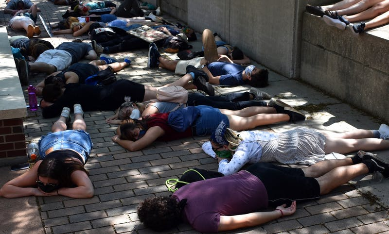 "Protesters lay on the ground outside of University of Minnesota Police Department headquarters as part of a ""die-in"" demanding the University disarm and defund UMPD on Sunday, June 7. They laid on the ground for eight minutes and 46 seconds to honor George Floyd."