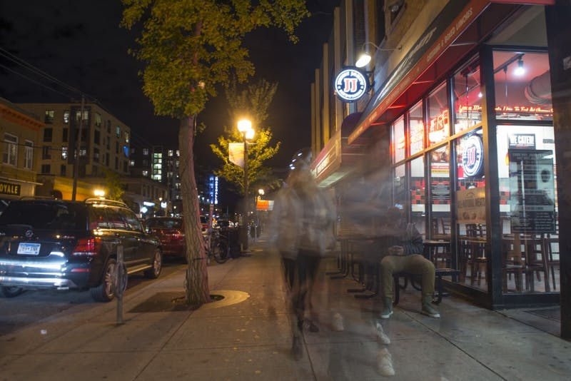 Pedestrians walk through Dinkytown Friday evening. Business owners in the neighborhood are pushing for more security cameras in an effort to stem crime in the area.