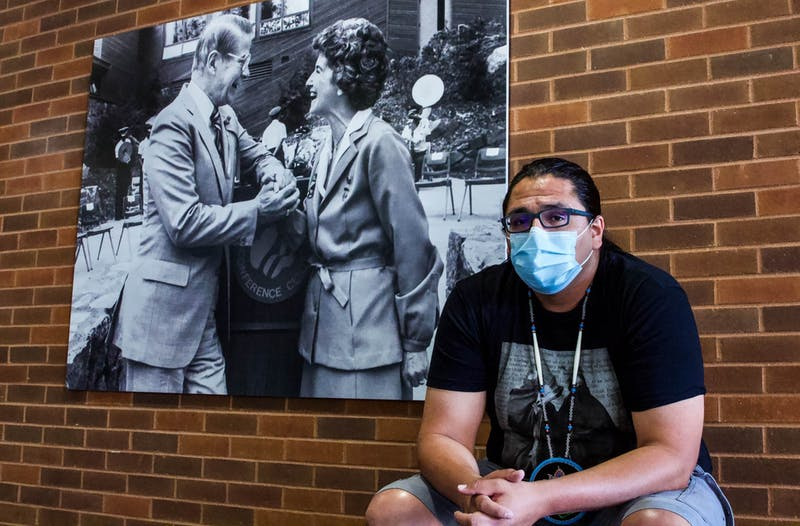 Benjamin Yawakie, president of the Humphrey Students of Color Association, sits in front of a photo of Orville and Jane Freeman in the Humphrey School of Public Affairs on Wednesday, July 22 at the University of Minnesota, Twin Cities campus. The Freeman Commons, to Yawakie's left, is one of the spaces on campus associated with the Freemans that the group wants to rename.